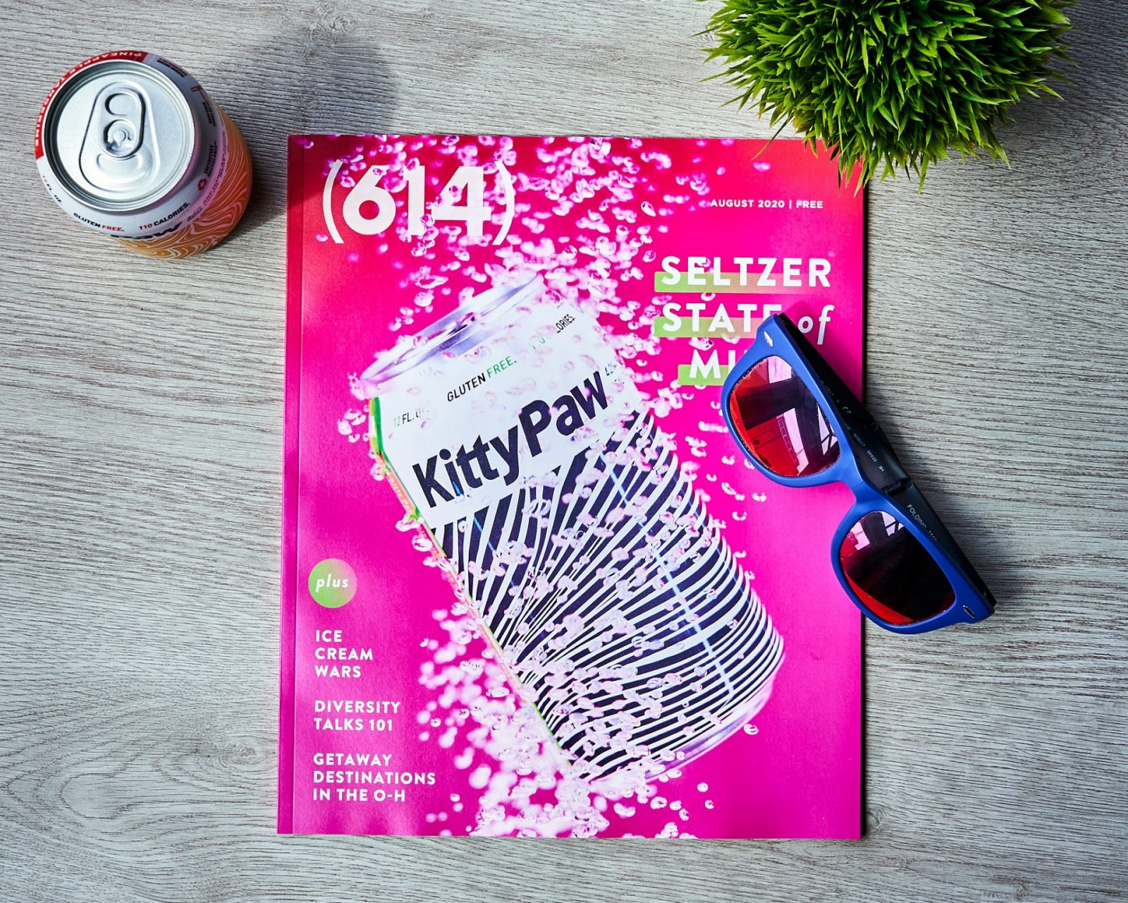 614 magazine August cover, hot pink with can of hard seltzer. Magazine is surrounded by a can of seltzer, a plant, and sunglasses.